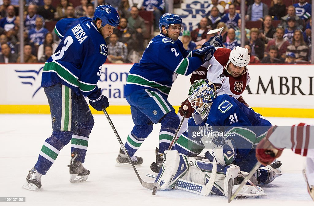 Kevin Bieksa #3 of the Vancouver Canucks clears the puck after goalie Eddie Lack #31 makes the initial save while Dan Hamhuis #2 and Kyle Chipchura #24 of the Arizona Coyotes battle for position in from of the net in NHL action on April 9, 2015 at Rogers Arena in Vancouver, British Columbia, Canada.