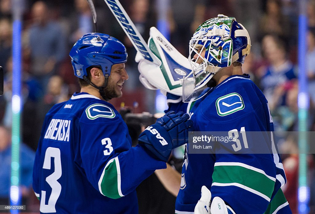Kevin Bieksa #3 of the Vancouver Canucks congratulates goalie Eddie Lack #31 after defeating the Arizona Coyotes 5-0 in NHL action on April 9, 2015 at Rogers Arena in Vancouver, British Columbia, Canada.