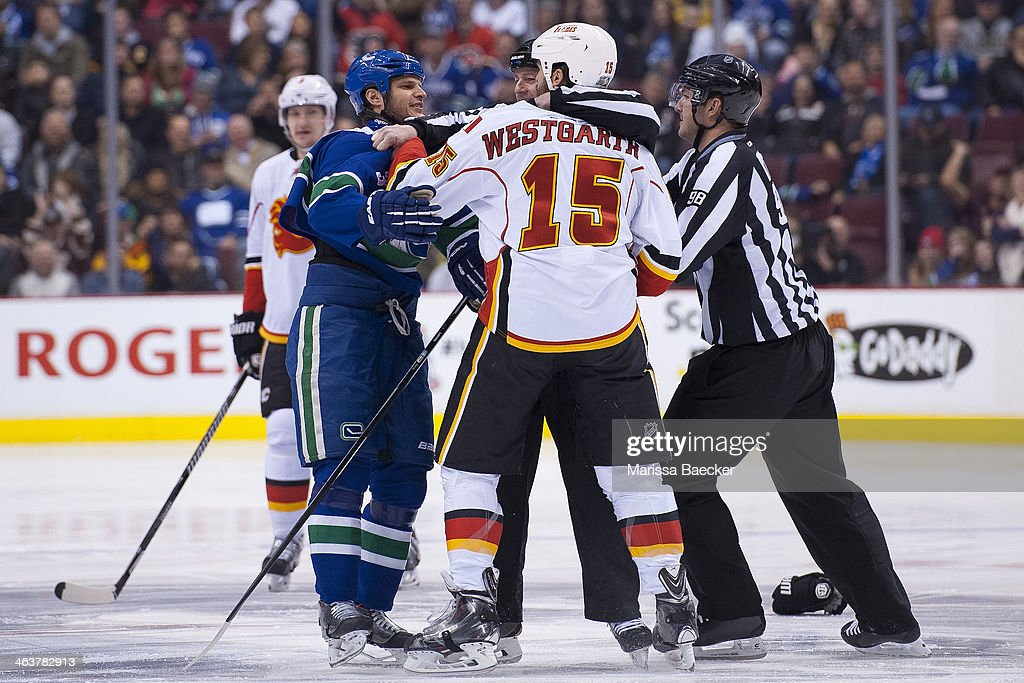 Kevin Bieksa #3 of the Vancouver Canucks is separated from Kevin Westgarth #15 of the Calgary Flames by referees after the opening puck drop on January 18, 2014 at Rogers Arena in Vancouver, British Columbia, Canada.