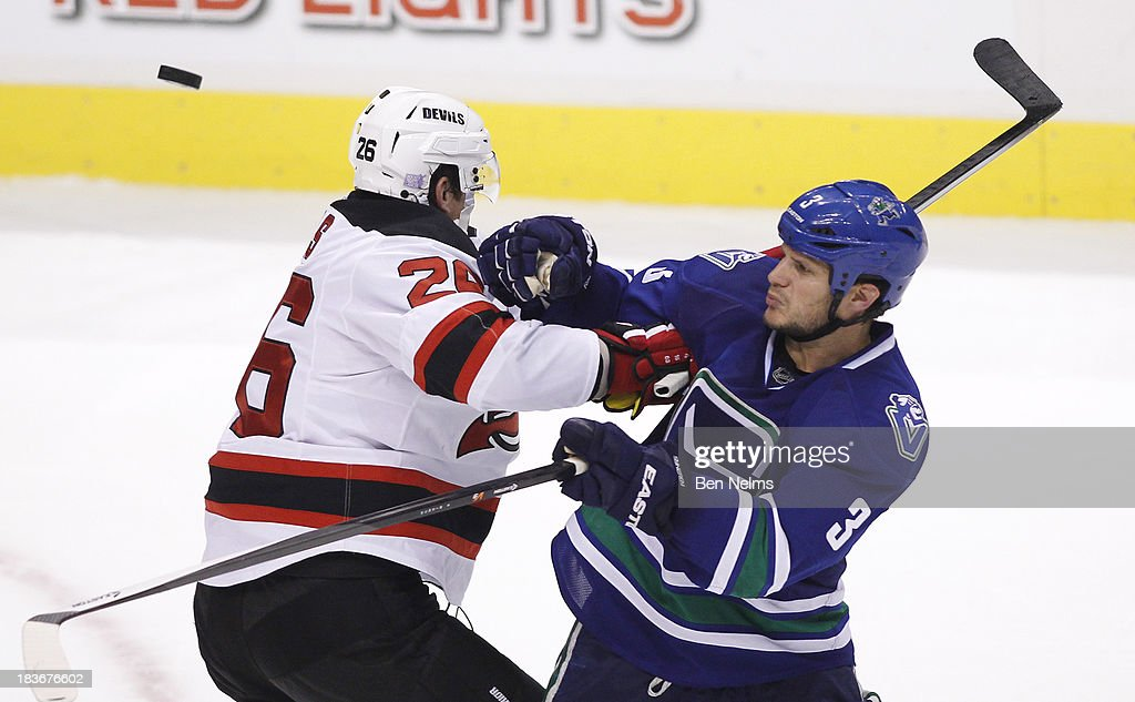<a gi-track='captionPersonalityLinkClicked' href=/galleries/search?phrase=Kevin+Bieksa&family=editorial&specificpeople=688792 ng-click='$event.stopPropagation()'>Kevin Bieksa</a> #3 of the Vancouver Canucks keeps his eye on the puck near<a gi-track='captionPersonalityLinkClicked' href=/galleries/search?phrase=Patrik+Elias&family=editorial&specificpeople=201827 ng-click='$event.stopPropagation()'>Patrik Elias</a> #26 of the New Jersey Devils during the third period of their NHL game at Rogers Arena on October 8, 2013 in Vancouver, British Columbia, Canada.