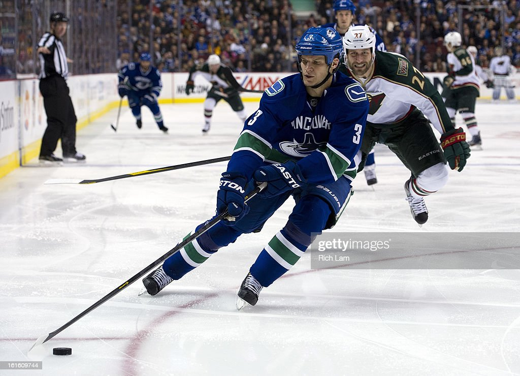 <a gi-track='captionPersonalityLinkClicked' href=/galleries/search?phrase=Kevin+Bieksa&family=editorial&specificpeople=688792 ng-click='$event.stopPropagation()'>Kevin Bieksa</a> #3 of the Vancouver Canucks picks up the loose puck while being pressured by Mike Rupp #27 of the Minnesota Wild during the third period in NHL action on February 12, 2013 at Rogers Arena in Vancouver, British Columbia, Canada.