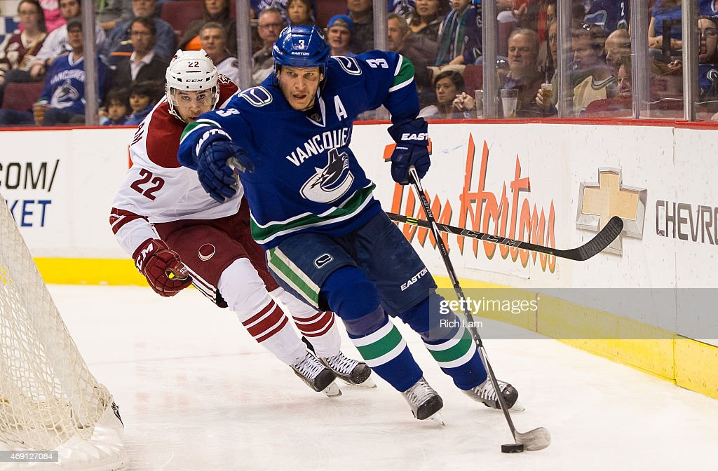 Kevin Bieksa #3 of the Vancouver Canucks picks up the loose puck while pressured by Craig Cunningham #22 of the Arizona Coyotes in NHL action on April 9, 2015 at Rogers Arena in Vancouver, British Columbia, Canada.