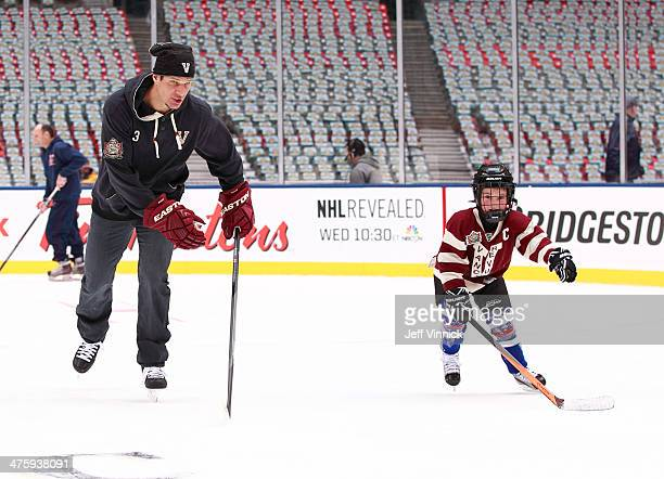Kevin Bieksa of the Vancouver Canucks races his son Cole Bieksa during a family skate at the 2014 Tim Hortons NHL Heritage Classic at BC Place...