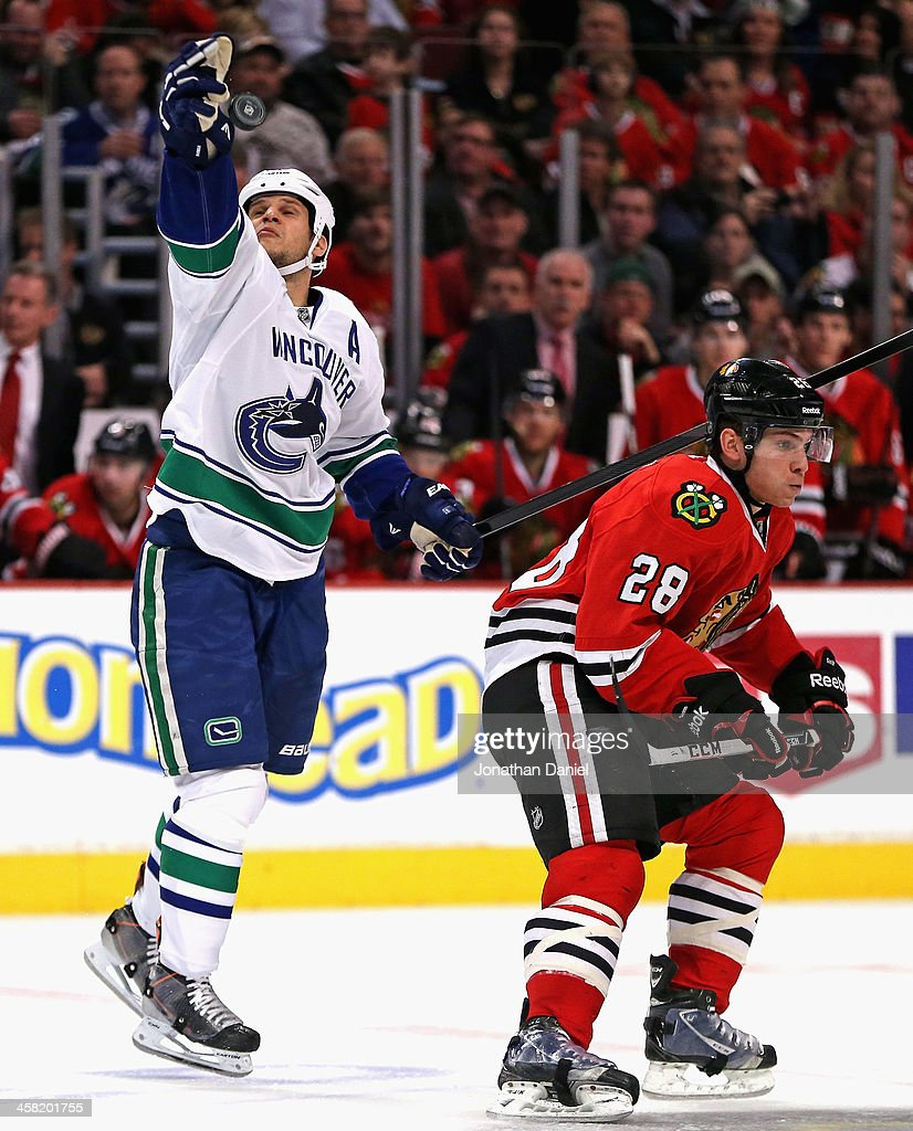 <a gi-track='captionPersonalityLinkClicked' href=/galleries/search?phrase=Kevin+Bieksa&family=editorial&specificpeople=688792 ng-click='$event.stopPropagation()'>Kevin Bieksa</a> #3 of the Vancouver Canucks reaches for the puck in air behind Ben Smith #28 of the Chicago Blackhawks at the United Center on December 20, 2013 in Chicago, Illinois.