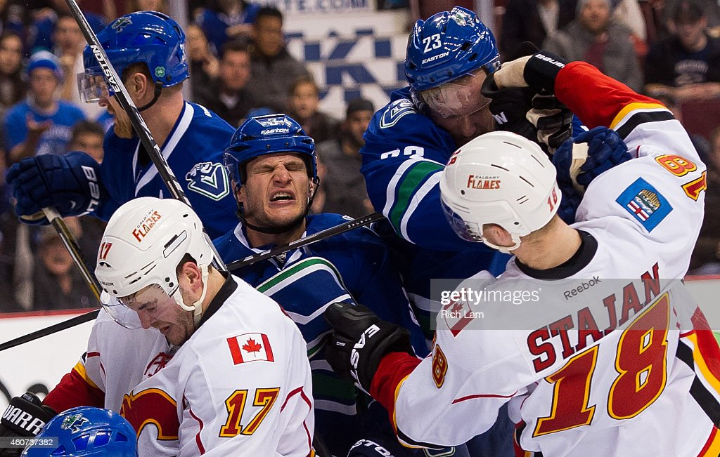 Kevin Bieksa #3 of the Vancouver Canucks reacts after getting hit while in a scrum while Alexander Edler #23 battles with Matt Stajan #18 of the Calgary Flames during the second period in NHL action on December 20, 2014 at Rogers Arena in Vancouver, British Columbia, Canada. Lance Bouma #17 and Henrik Sedin #33 also take part in the scrum.