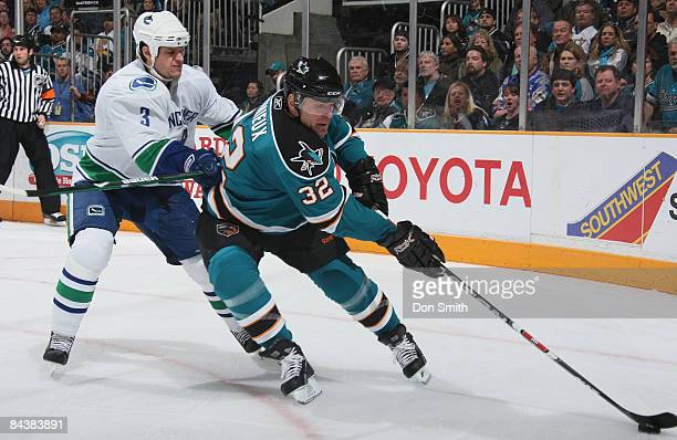Kevin Bieksa of the Vancouver Canucks tries to stop Claude Lemieux of the San Jose Sharks who maneuvers the puck down the ice during an NHL game on...