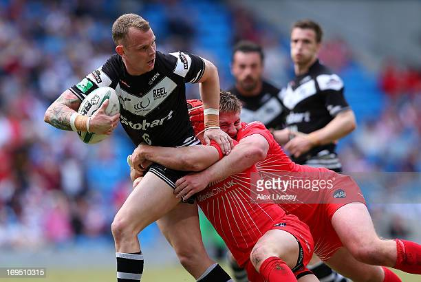 Kevin Brown of Widnes Vikings is tackled by Wayne Godwin and Jake Emmitt of Salford City Reds during the Magic Weekend at Etihad Stadium on May 26...
