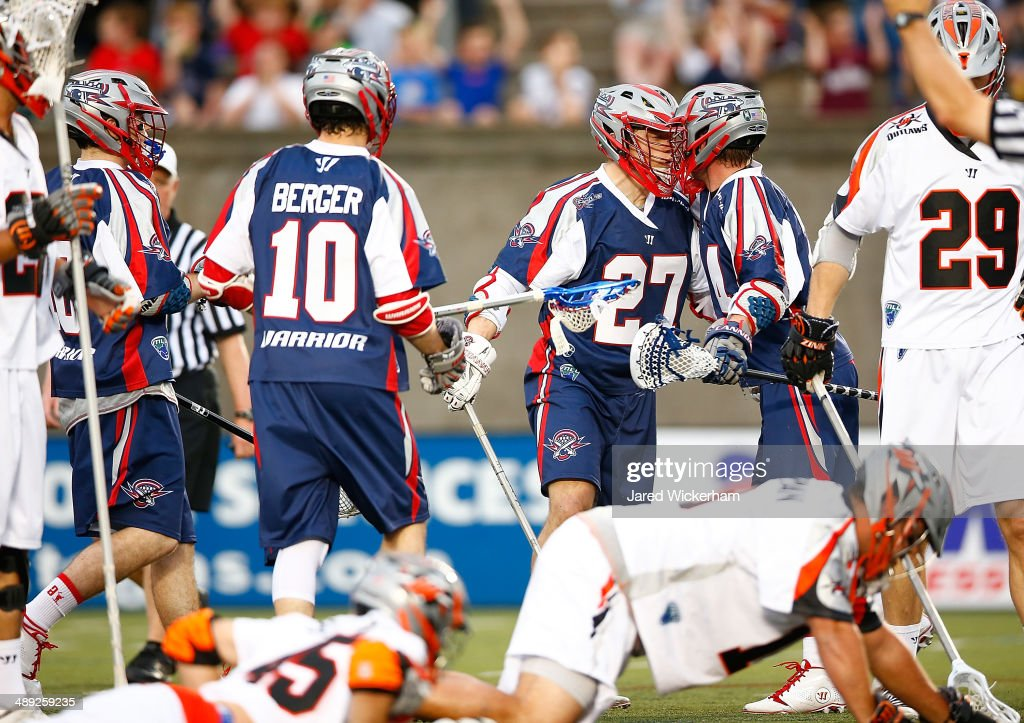 Kevin Buchanan #27 of the Boston Cannons celebrates a goal in the first half with teammates against the Denver Outlaws at Harvard Stadium on May 10, 2014 in Boston, Massachusetts.