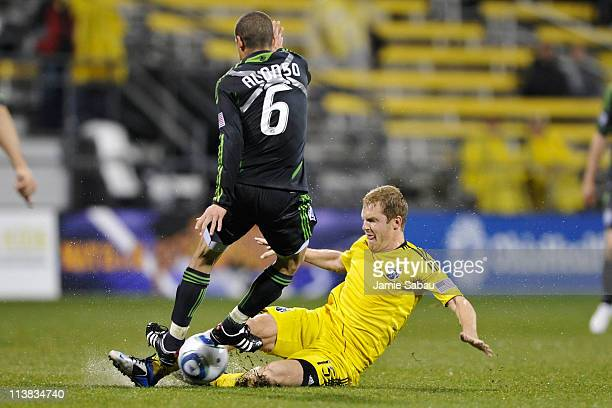 Kevin Burns of the Columbus Crew slides in to kick the ball away from Osvaldo Alonso of the Seattle Sounders in the second half on May 7 2011 at Crew...