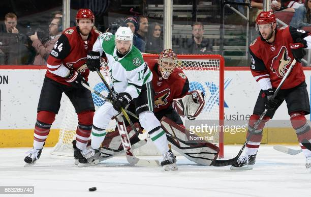 Kevin Connauton of the Arizona Coyotes and Devin Shore of the Dallas Stars battle for position in front of goalie Adin Hill and Jason Demers of the...