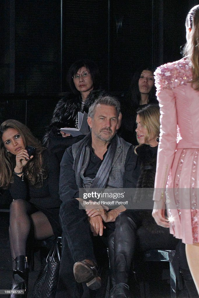 Kevin Costner (C) and his wife Christine (R) attend the Versace Spring/Summer 2013 Haute-Couture show as part of Paris Fashion Week at Le Centorial on January 20, 2013 in Paris, France.
