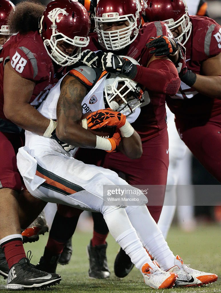 Kevin Cummings #84 of the Oregon State Beavers is tackled by Kalafitoni Pole #98 and Xavier Cooper #96 of the Washington State Cougars during the game at Martin Stadium on October 12, 2013 in Pullman, Washington.