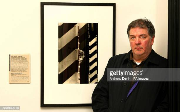 Kevin Cummins poses with his portrait of Tony Wilson taken at Manchester's Hacienda nightclub in 1985 as it goes on display in the National Portrait...
