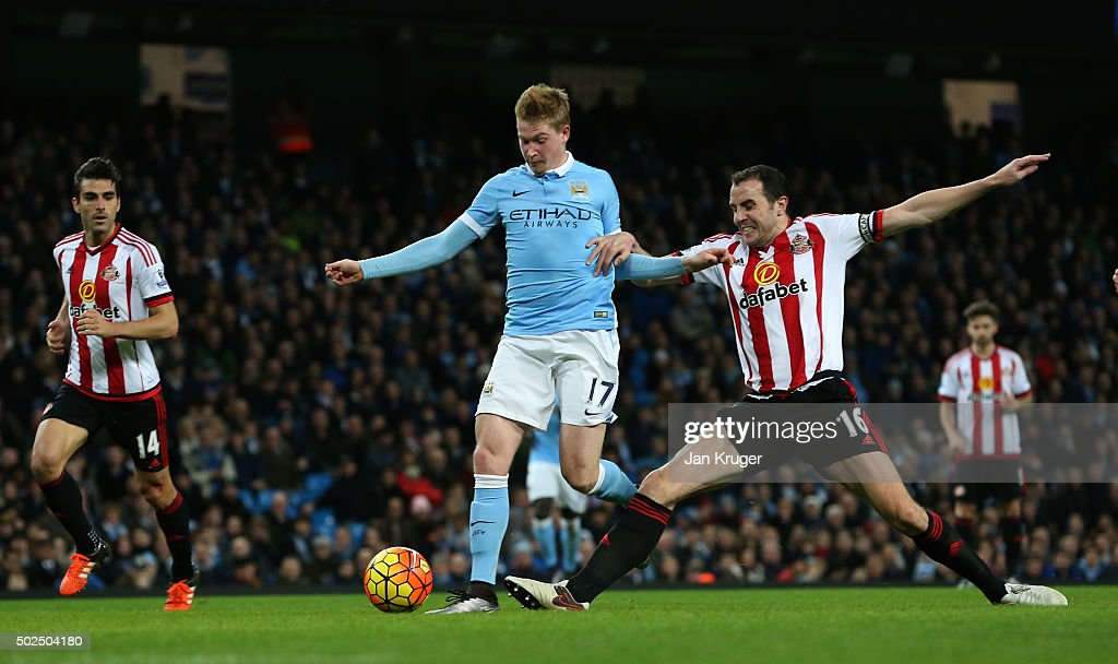<a gi-track='captionPersonalityLinkClicked' href=/galleries/search?phrase=Kevin+De+Bruyne&family=editorial&specificpeople=6165471 ng-click='$event.stopPropagation()'>Kevin De Bruyne</a> of Manchester City holds off the challenge from <a gi-track='captionPersonalityLinkClicked' href=/galleries/search?phrase=John+O%27Shea+-+Soccer+Player&family=editorial&specificpeople=202487 ng-click='$event.stopPropagation()'>John O'Shea</a> of Sunderland to score his team's fourth goal during the Barclays Premier League match between Manchester City and Sunderland at the Etihad Stadium on December 26, 2015 in Manchester, England.