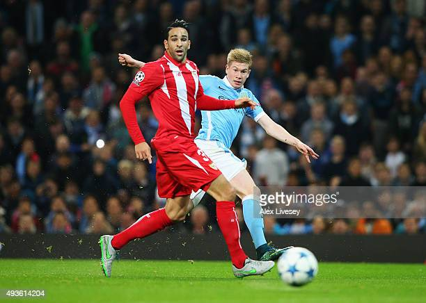 Kevin De Bruyne of Manchester City shoots under pressure from Adil Rami of Sevilla during the UEFA Champions League Group D match between Manchester...