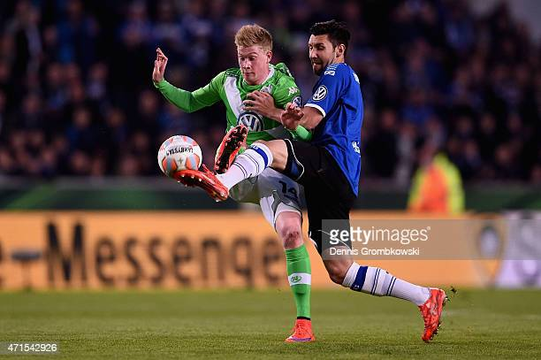 Kevin De Bruyne of VfL Wolfsburg is challenged by Stephan Salger of Arminia Bielefeld during the DFB Cup Semi Final match betwen Arminia Bielefeld...
