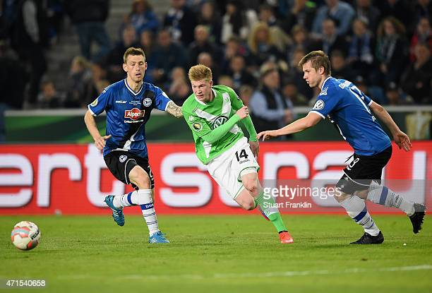 Kevin De Bruyne of Wolfsburg is challenged by Manuel Junglas of Bielefeld and Julian Boerner of Bielefeld during the DFB Cup Semi Final match between...