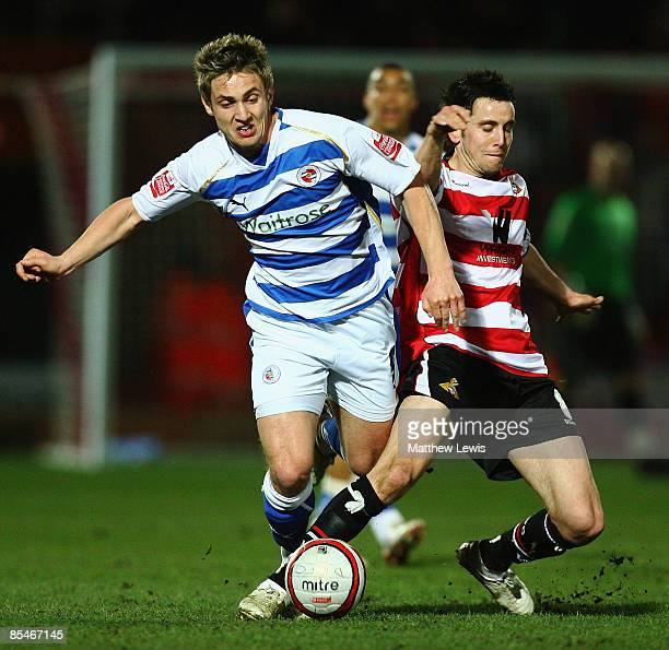 Kevin Doyle of Reading beats the challenge from Brian Stock of Doncaster during the CocaCola Championship match between Doncaster Rovers and Reading...