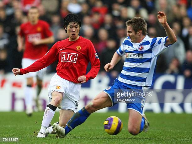 Kevin Doyle of Reading challenges JiSung Park of Manchester United during the Barclays Premier League match between Reading and Manchester United at...