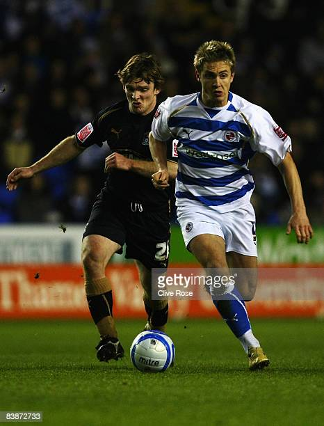 Kevin Doyle of Reading is challenged by Ben Turner of Coventry City during the CocaCola Championship match between Reading and Coventry at the...
