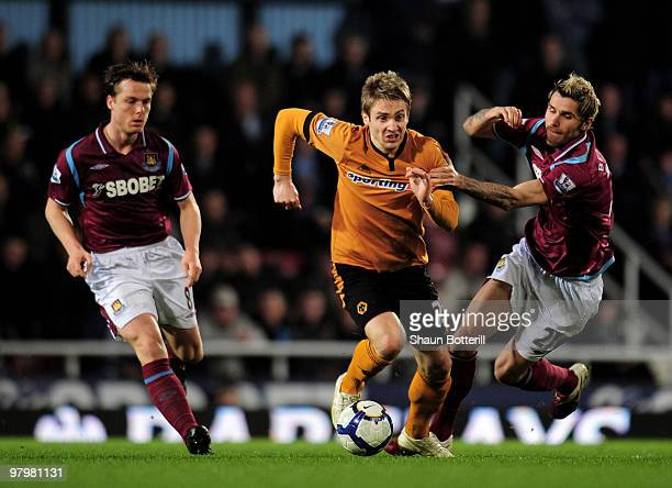 Kevin Doyle of Wolverhampton Wanderers is challenged by Valon Behrami and Scott Parker of West Ham United during the Barclays Premier League match...