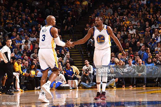 Kevin Durant and David West of the Golden State Warriors high five each other during the game against the Indiana Pacers on December 5 2016 at ORACLE...