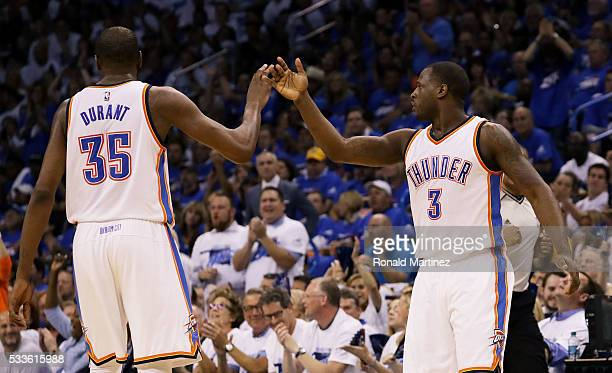 Kevin Durant and Dion Waiters of the Oklahoma City Thunder celebrate in the second quarter against the Golden State Warriors and in game three of the...