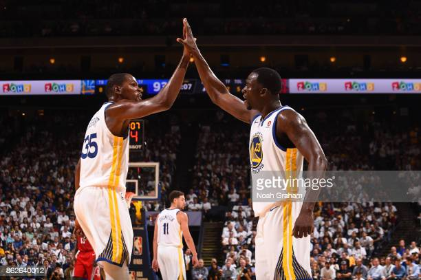 Kevin Durant and Draymond Green of the Golden State Warriors high five during the game against the Houston Rockets on October 17 2017 at ORACLE Arena...