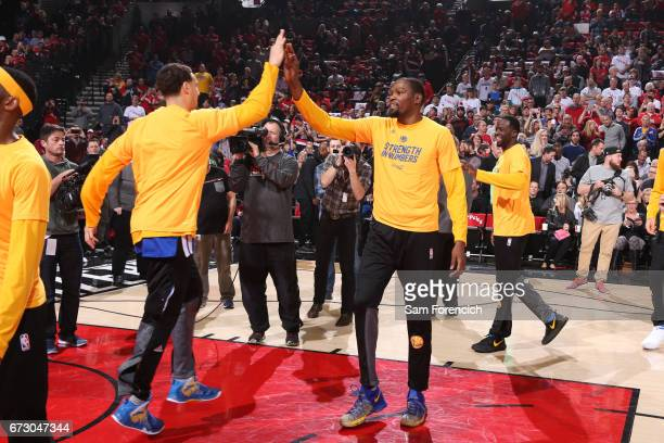 Kevin Durant and Klay Thompson of the Golden State Warriors high five before the game against the Portland Trail Blazers during Game Four of the...