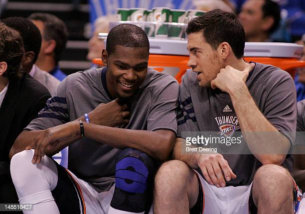 Kevin Durant and Nick Collison of the Oklahoma City Thunder talk on the bench late in the fourth quarter while taking on the San Antonio Spurs in...