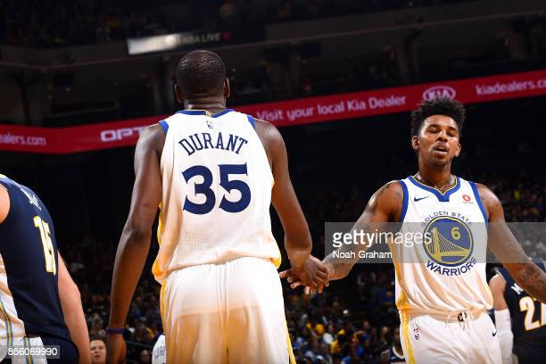 Kevin Durant and Nick Young of the Golden State Warriors high five each other during the game against the Denver Nuggets during a preseason game on...