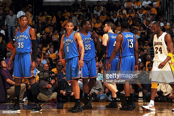 Kevin Durant and Russell Westbrook of the Oklahoma City Thunder eye Kobe Bryant of the Los Angeles Lakers as he walks near by in Game One of the...