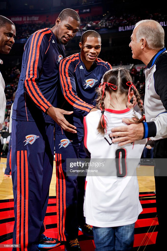 Kevin Durant #35 and Russell Westbrook #0 of the Oklahoma City Thunder greet a young Portland Trail Blazers fan before the two teams played on January 13, 2013 at the Rose Garden Arena in Portland, Oregon.