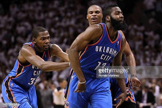 Kevin Durant and Russell Westbrook of the Oklahoma City Thunder celebrate with James Harden after he hit a three pointer late in the game against the...