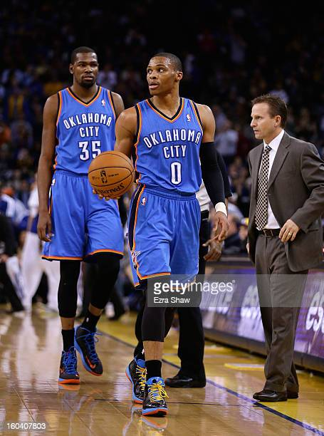 Kevin Durant and Russell Westbrook walk past head coach Scott Brooks of the Oklahoma City Thunder during their game against the Golden State Warriors...