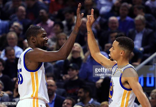 Kevin Durant and Steph Curry of the Golden State Warriors high five during the first half of an NBA game against the Toronto Raptors at Air Canada...