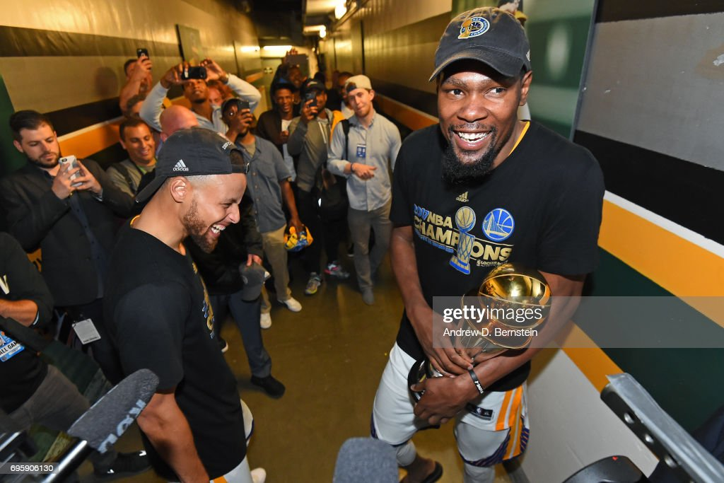Kevin Durant #35 and Stephen Curry #30 of the Golden State Warriors celebrate in the hallway after winning the NBA Championship in Game Five of the 2017 NBA Finals against the Cleveland Cavaliers on June 12, 2017 at ORACLE Arena in Oakland, California.