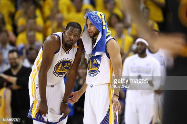 Kevin Durant and Stephen Curry of the Golden State Warriors discuss the play against the Cleveland Cavaliers during the second half in Game 5 of the...