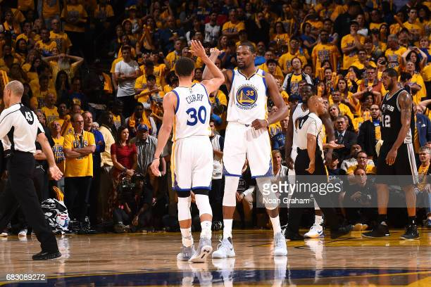 Kevin Durant and Stephen Curry of the Golden State Warriors high five each other during the game against the San Antonio Spurs during Game One of the...