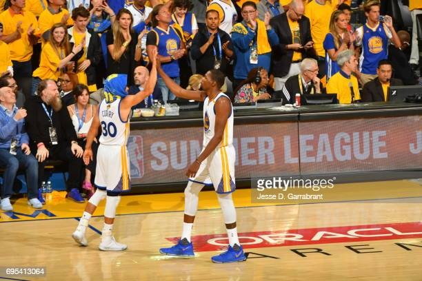 Kevin Durant and Stephen Curry of the Golden State Warriors high five each other during the game against the Cleveland Cavaliers in Game Five of the...