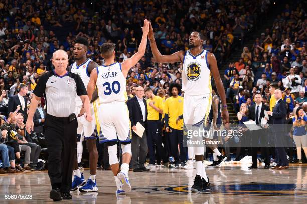 Kevin Durant and Stephen Curry of the Golden State Warriors high five each other during the game against the Denver Nuggets during a preseason game...