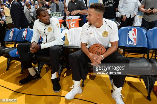Kevin Durant and Stephen Curry of the Golden State Warriors talk on the bench before the game against the Houston Rockets on October 17 2017 at...