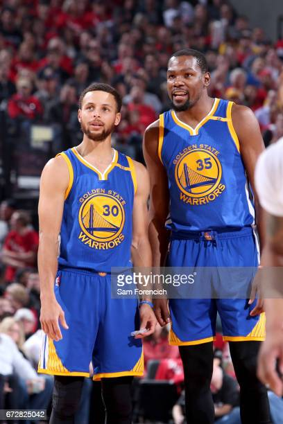 Kevin Durant and Stephen Curry of the Golden State Warriors talk during the game against the Portland Trail Blazers during Game Four of the Western...