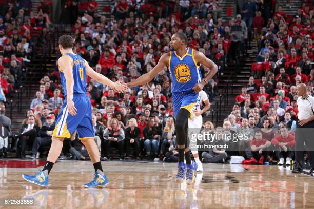 Kevin Durant high fives Klay Thompson of the Golden State Warriors during the game against the Portland Trail Blazers during Game Four of the Western...