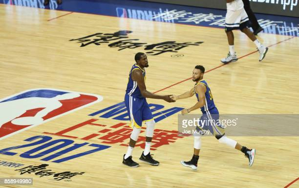 Kevin Durant high fives Stephen Curry of the Golden State Warriors against the Minnesota Timberwolves as part of the 2017 Global Games China on...