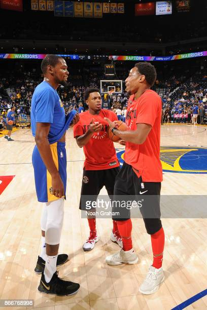 Kevin Durant of the Golden State Warriors and Kyle Lowry and DeMar DeRozan of the Toronto Raptors talk before the game on October 25 2017 at ORACLE...