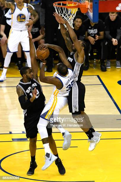 Kevin Durant of the Golden State Warriors attempts a shot against Kawhi Leonard and LaMarcus Aldridge of the San Antonio Spurs during Game One of the...