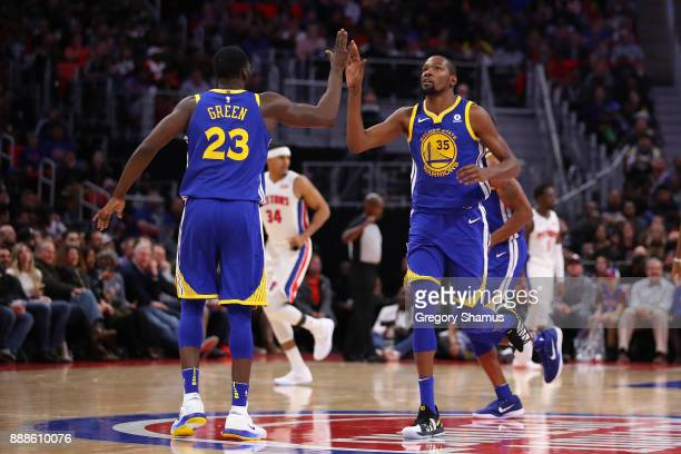 Kevin Durant of the Golden State Warriors celebrates a basket with Draymond Green while playing the Detroit Pistons during the second half at Little...