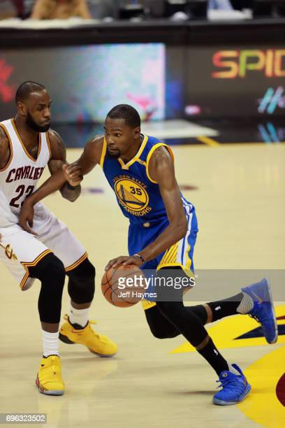 Kevin Durant of the Golden State Warriors dribbles the ball against LeBron James of the Cleveland Cavaliers in Game Four of the 2017 NBA Finals on...