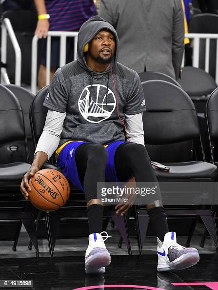 Kevin Durant of the Golden State Warriors dribbles the ball while sitting on the bench before a preseason game against the Los Angeles Lakers at...